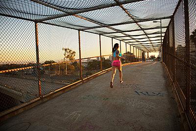 Female jogger running on walkway - p429m872920 by Corey Jenkins