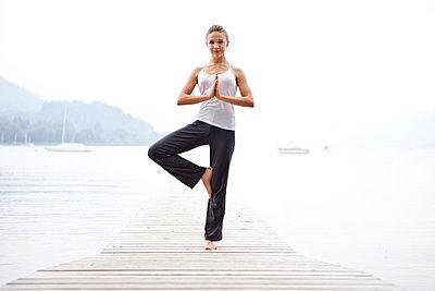 Junge Frau macht eine Yogaübung an einem See - p473m923088f von STOCK4B-RF