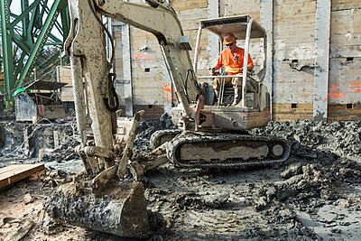 Caucasian worker using digger at construction site - p555m1305991 by Don Mason