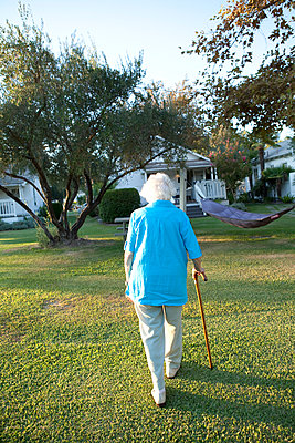 Caucasian woman walking with cane in backyard - p555m1408865 by Shestock