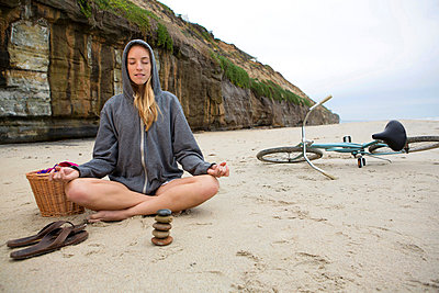 Woman meditating with rocks on beach - p924m807198f by InStock