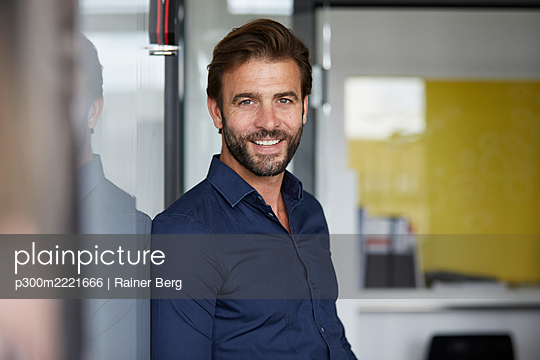 Man smiling while leaning on wall in office - p300m2221666 by Rainer Berg