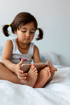 Little girl sitting on bed holding smartphone with feet, close-up - p300m2180693 by Valentina Barreto