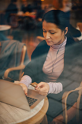 High angle view of businesswoman doing online shopping over laptop while sitting in cafe seen through window - p426m2075137 by Maskot