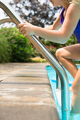 Caucasian girl climbing out of swimming pool - p555m1421668 by JGI/Jamie Grill