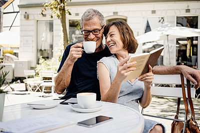Mature couple drinking coffee in a sidewalk cafe - p586m2109185 by Kniel Synnatzschke