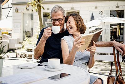 Seniorenpaar trinkt Kaffee in einem Straßencafe - p586m2109185 von Kniel Synnatzschke