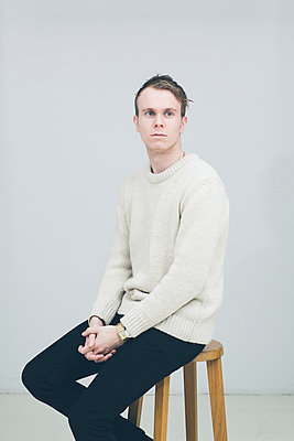 Young man sits on barstool  - p686m1042576 by Paul Tait
