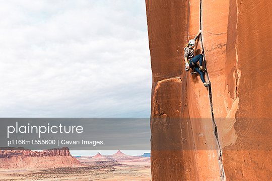 Side view of female hiker rock climbing against sky - p1166m1555600 by Cavan Images