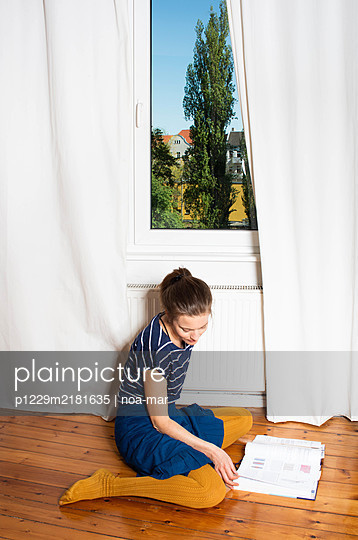 Young woman leafing through book, Stay at home due to Covid-19 - p1229m2181635 by noa-mar