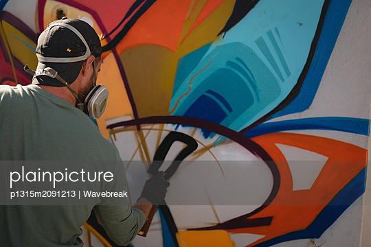 Graffiti artist spray painting on weathered wall  - p1315m2091213 by Wavebreak