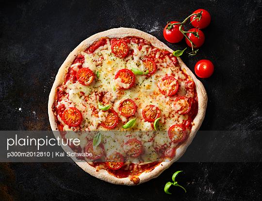 Pizza Margherita and cherry tomatoes on dark ground - p300m2012810 by Kai Schwabe
