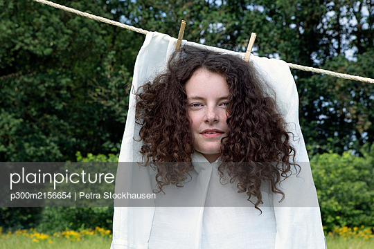 Portrait of young woman with brown ringlets in white dress drying on clothesline - p300m2156654 by Petra Stockhausen