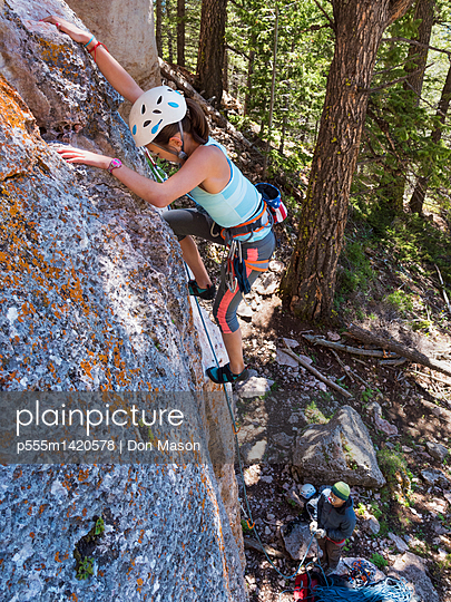 Mixed race girl climbing steep cliff - p555m1420578 by Don Mason