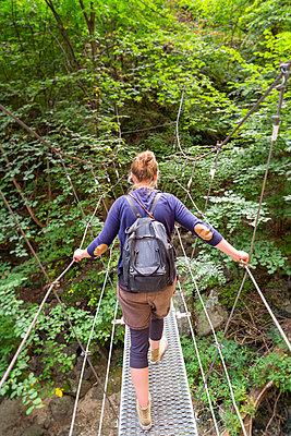 Hiker crossing metal suspension bridge on hiking trail. - p1166m2136804 by Cavan Images