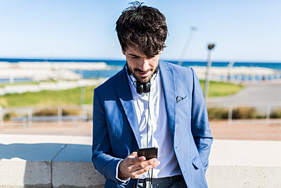 Young businessman looking at smartphone outdoors - p300m1460045 by Giorgio Fochesato
