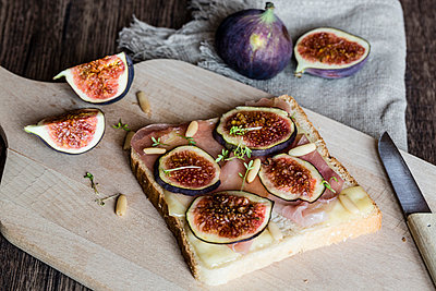 Toast garnished with cheese, ham, slices of fig, pine nuts and cress - p300m975340f by Sandra Roesch