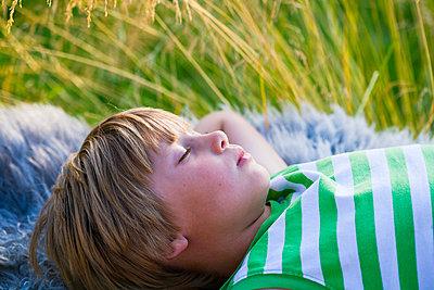 Boy sleeping on blanket outdoors - p312m695531 by Plattform photography