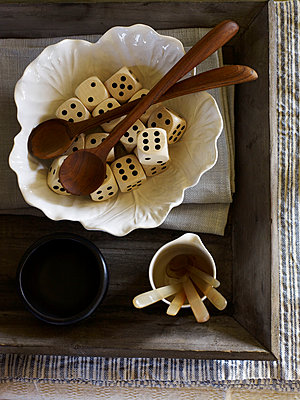 Wooden spoons and dice in ceramic bowl in crate. - p349m2167720 by Polly Wreford