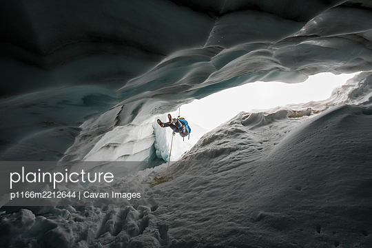 Mountain climber rappelling into crevasse / glacial ice cave. - p1166m2212644 by Cavan Images