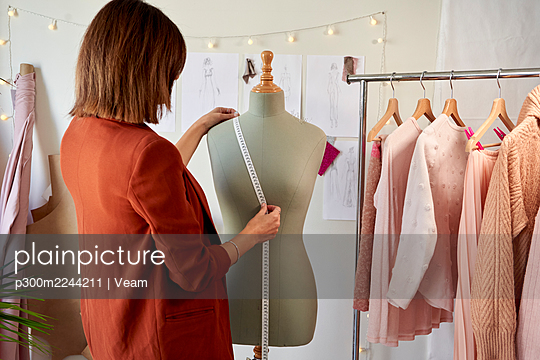 Female fashion entrepreneur measuring dressmaker's model by clothes rack at design studio - p300m2244211 by Veam
