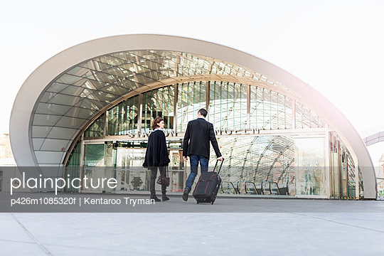 Rear view of business people talking while entering railway station - p426m1085320f by Kentaroo Tryman