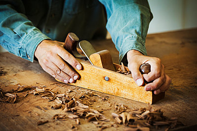 A workman using a hand wood plane on the surface of a large piece of wood.  - p1100m1522496 by Mint Images