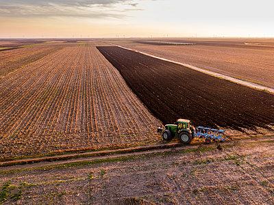 Serbia, Vojvodina. Tractor plowing field in the evening - p300m2069638 von oticki