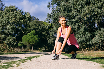 Smiling woman looking away while tying shoelace at footpath during sunny day - p300m2273485 by Andrés Benitez