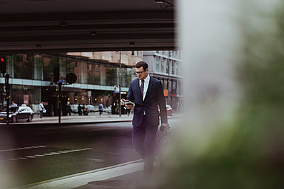 Businessman with bag using smart phone while walking in city - p426m2218811 by Maskot