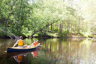 Father and son paddling canoe on river - p429m1450615 by Hugh Whitaker