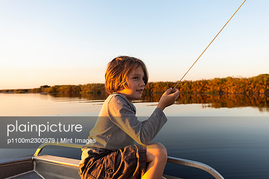 Young boy fishing from a boat on the Okavango Delta at sunset, Botswana. - p1100m2300979 by Mint Images