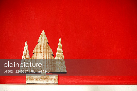 A wooden tree decoration against a red background - p1302m2245037 by Richard Nixon
