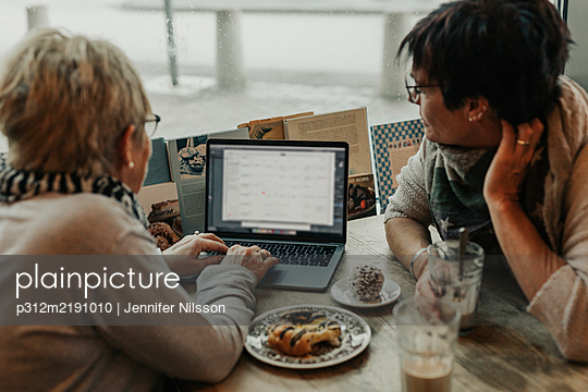 Women using laptop in cafe - p312m2191010 by Jennifer Nilsson