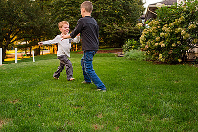 two small boys play together in yard - p1166m2084819 by Cavan Images