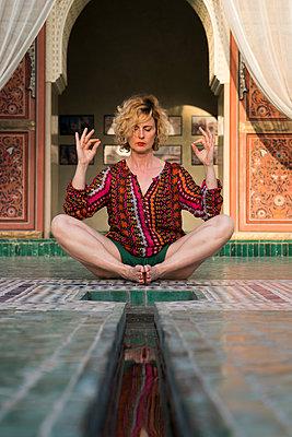 Morocco, Marrakesh, tourist sitting on the floor doing yoga - p300m1449353 by Kike Arnaiz
