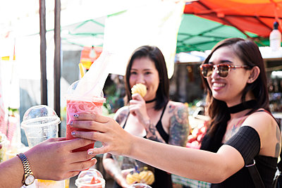 Woman buying a smoothie from a street vendor in Thailand - p300m1535723 by Ivan Gener Garcia