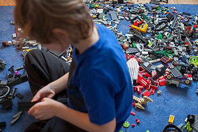 Sweden, Vastergotland, Lerum, Boy (8-9) playing with building blocks - p352m1079301f by Andreas Ulvdell
