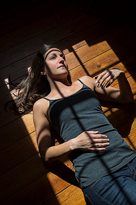 Junge Frau sonnt sich auf Holzfußboden - p397m1556572 von Peter Glass