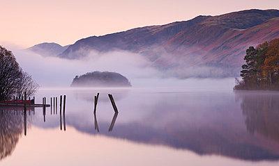 Mist surrounds a peaceful Derwent Water at dawn in autumn, Lake District National Park, Cumbria, England, United Kingdom, Europe - p8713041 by Adam Burton