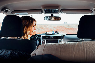Young woman driving vehicle in remote setting, rear view, vehicle interior, Mexican Hat, Utah, USA - p924m1580621 by Seth K. Hughes