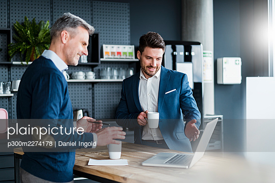 Business people discussing over laptop while having coffee in office cafe - p300m2274178 by Daniel Ingold