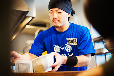A ramen noodle shop kitchen. A chef preparing bowls of ramen noodles in broth, a speciality and fast food dish.  - p1100m1185683 by Mint Images