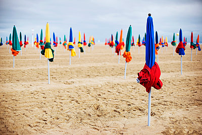 Closed parasols on sand at beach - p1166m1163641 by Cavan Images