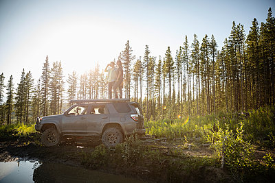 Couple enjoying overland adventure, standing on top of SUV in sunny remote forest, Alberta, Canada - p1192m2016522 by Hero Images