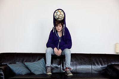 Junge mit Fussball in Kaputzenpulli - Blick in Kamera - p1212m1094449 von harry + lidy