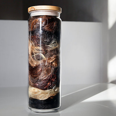 Various hair samples in a storage jar - p1519m2063294 by Soany Guigand
