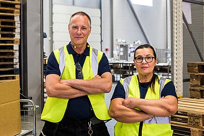 Portrait of confident coworkers standing with arms crossed in distribution warehouse - p426m2018862 by Maskot