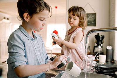 Girl washing mug while sister playing with cleaning brush at kitchen counter - p426m2118916 by Maskot