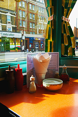 A restaurant table set with condiments and a menu, Shoreditch; London, England - p442m936391 by Ingrid Rasmussen